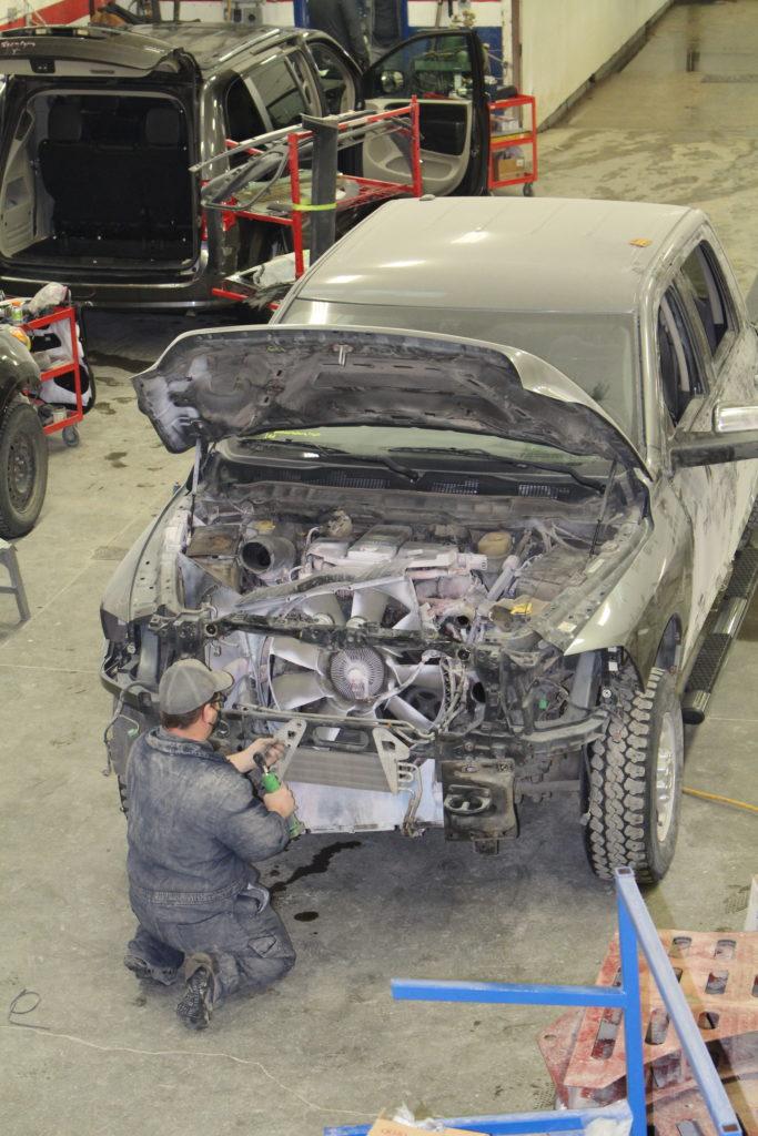 A specialist repairing auto damage at bergens regina